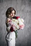 Cabelo encaracolado da menina bonita em um vestido branco com Fotos de Stock