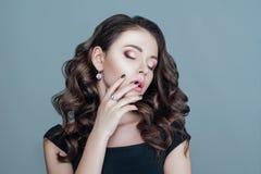 Cabelo encaracolado e joia modelo, composição violeta bonita, tratamento de mãos em pregos, penteado elegante Imagens de Stock Royalty Free