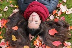Cabelo escuro longo da menina bonita decorado com folhas de outono imagens de stock