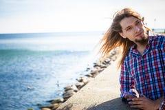 Cabelo longo do homem que relaxa pelo beira-mar Foto de Stock Royalty Free