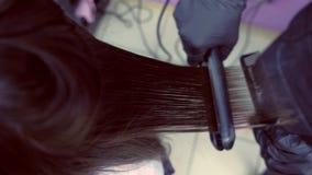 Cabelo marrom escuro dos straights do cabeleireiro da mulher bonita que usa tenazes de brasa do cabelo no salão de beleza Close-u vídeos de arquivo