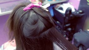 Cabelo marrom escuro dos straights do cabeleireiro da mulher bonita que usa tenazes de brasa do cabelo no sal?o de beleza filme