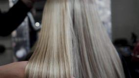 Cabelo para a extens?o do cabelo O cabelo para a extens?o do cabelo ? aplicado ? cabe?a 4K vídeos de arquivo