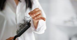 Cabelo perdedor da mulher na escova de cabelo à disposição, foco macio imagem de stock royalty free
