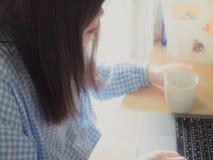 Cabelo preto com o pano azul do copo asiático da posse da mulher de negócio e Fotografia de Stock