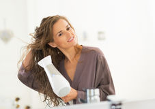 Cabelo secando da jovem mulher feliz no banheiro Imagens de Stock