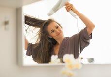 Cabelo secando da jovem mulher no banheiro Imagem de Stock