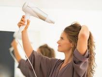 Cabelo secando da jovem mulher no banheiro Imagens de Stock