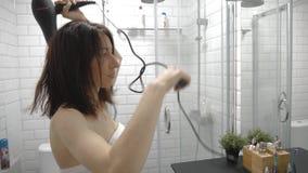 Cabelo secando da mulher feliz nova no banheiro, estilo de vida Conceito da beleza do penteado vídeos de arquivo