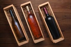 Cabernet and Chardonnay wine bottles in individual cases. Three Wine Boxes: Blush, Cabernet and Chardonnay wine bottles in individual cases with packing straw stock image