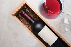 Cabernet - Sauvignon: Een fles in houten geval met een glas van rode wi royalty-vrije stock afbeelding