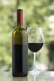 Cabernet wine. Open wine bottle and glass, on marble surface, outdoors background Stock Photos