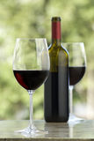 Cabernet wine. Glass of red wine, bottle and second glass in background, outdoors, nice glow in front glass Stock Photos
