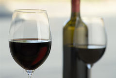 Cabernet wine. Close up of wine glass,red glow of wine visible, bottle and second glass soft focus in background, outdoors Stock Images
