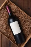 Cabernet Wine Bottle in Packing Straw. High angle shot of a single bottle with blank label in a cardboard box with straw packing Stock Image