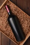 Cabernet Wine Bottle in Packing Straw. High angle shot of a single bottle with no label in a cardboard box with straw packing Stock Photos