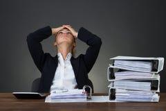 Cabeza cansada de With Hands On de la empresaria en el escritorio foto de archivo libre de regalías