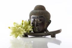 Cabeza de Buda en un fondo, una toalla, piedras y un loto blancos Fotos de archivo libres de regalías
