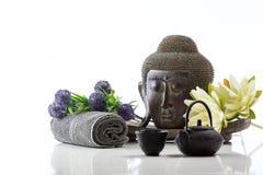 Cabeza de Buda en un fondo, una toalla, una tetera y un loto blancos Foto de archivo