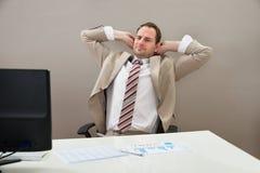 Cabeza de With Hands Behind del hombre de negocios en oficina foto de archivo libre de regalías