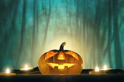 Cabeza de la calabaza de Halloween con la luz de la vela en madera fantasmagórica de la oscuridad Foto de archivo