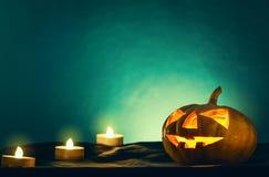 Cabeza de la calabaza de Halloween con la luz de la vela en parte posterior fantasmagórica de la oscuridad Foto de archivo libre de regalías