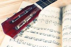 Cabeza de la guitarra en notas de una música Fotos de archivo libres de regalías