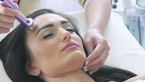 Cabeza de la mujer joven que tiene masaje facial del ultrusound eléctrico en el salón de belleza metrajes