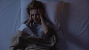 Cabeza de la tenencia de la muchacha que miente en la cama, intentando caer dormido en apresurar el ?rea de la ciudad metrajes