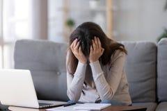 Cabeza de la tenencia de la mujer del trastorno en sentarse frustrado manos cerca del ordenador portátil foto de archivo libre de regalías