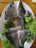 Cabeza de los pescados de mar en una placa blanca adornada con las verduras frondosas verdes foto de archivo libre de regalías