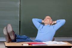 Cabeza de profesor With Hands Behind que mira para arriba el escritorio imagenes de archivo
