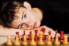 Cabeza de reclinación del adolescente en la tabla cerca del tablero de ajedrez Imagenes de archivo