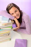 Cabeza de reclinación sonriente de la muchacha del estudiante en los libros Fotografía de archivo libre de regalías