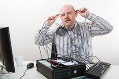 Cabeza de Touching Cables On del hombre de negocios mientras que repara el ordenador Fotos de archivo libres de regalías
