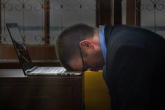 Cabeza del hombre de negocios abajo en su labtop Imágenes de archivo libres de regalías