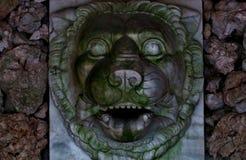 Cabeza del metal de un león en una pared de piedra fluyó de qué agua una vez imagen de archivo libre de regalías