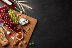 Cabeza del queso, manojo de uvas, miel, nueces y copa en el tablero de madera y el fondo negro fotografía de archivo libre de regalías