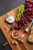 Cabeza del queso, manojo de uvas, miel, nueces y copa en el tablero de madera y el fondo negro fotos de archivo