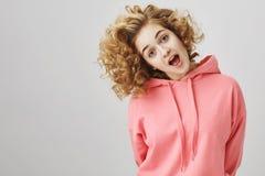 Cabeza inclinable de la muchacha rizado-cabelluda joven emotiva juguetona, echando un vistazo en la cámara con la boca abierta co Imagen de archivo libre de regalías