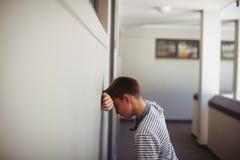 Cabeza que se inclina del colegial triste contra la pared en pasillo Imagen de archivo