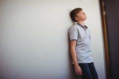 Cabeza que se inclina del colegial triste contra la pared en pasillo Imágenes de archivo libres de regalías