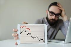 Cabeza que se inclina del hombre de negocios deprimido debajo de la mala carta del mercado de acción Imagen de archivo