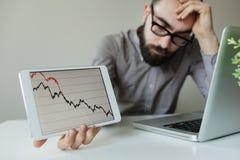 Cabeza que se inclina del hombre de negocios deprimido debajo de la mala carta del mercado de acción Foto de archivo