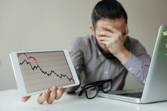 Cabeza que se inclina del hombre de negocios deprimido debajo de la mala carta del mercado de acción Imagen de archivo libre de regalías