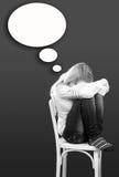 El sentarse de la mujer joven triste o deprimido en silla Fotografía de archivo libre de regalías