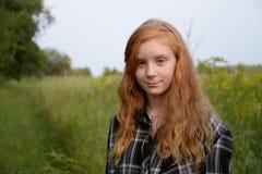 Cabeza roja del pelo largo del tween con paisaje verde Imágenes de archivo libres de regalías