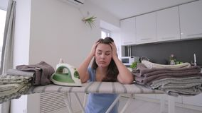 Cabeza triste cansada de la tenencia del ama de casa en la desesperación mientras que plancha durante tareas de hogar almacen de video