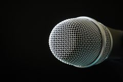 Cabeza y parrilla del micrófono aisladas en negro fotografía de archivo