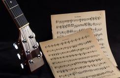 Cabezal de la guitarra con partitura Fotografía de archivo
